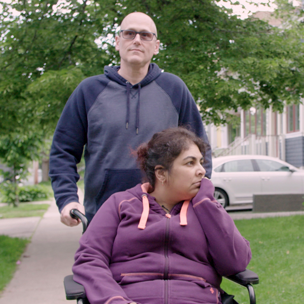Image of Dr Shelly Sarwal in a wheelchair and Randy Tresidder behind pushing the wheelchair while going out for a stroll