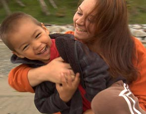 Young boy held by his mother while laughing