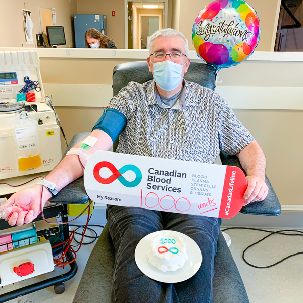 Image of blood donor Allen Veal holding up a My Reasons sign while sitting in a chair donating blood at the Charlottetown, PEI donor centre