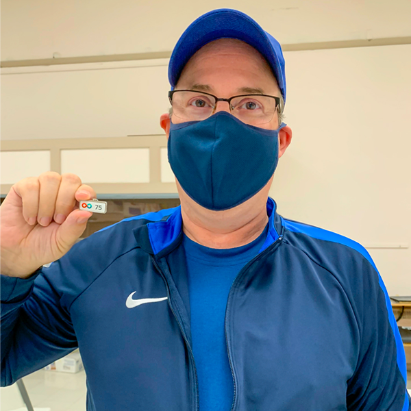 Image of Geoff Van Geem holding a pin while wearing a mask