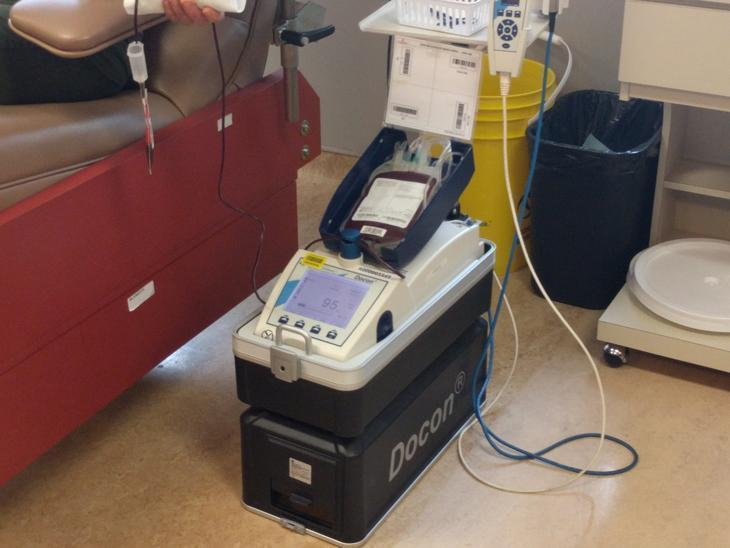 Nothing unusual is going on here: You'll find all the same bags, tubes and monitoring equipment used in a regular donation clinic.  [Blood donation in progress, with blood flowing through the tube from patient to blood bag.]