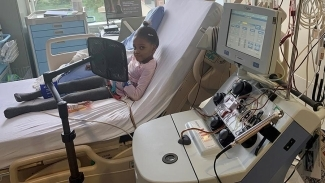 Aaliyah Mchopanga receiving red cell treatment sitting hospital bed