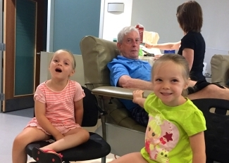 Brian Boyd donates blood with his twin granddaughters Lillian and Violet Boyd.