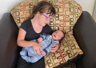 Chloe Morrell holds her newborn brother, Connor. Connor's mother donated his umbilical cord blood to Canadian Blood Services' Cord Blood Bank.