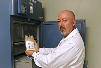 Craig Jenkins, senior manager of product and process development, removes a unit of plasma from a freezer