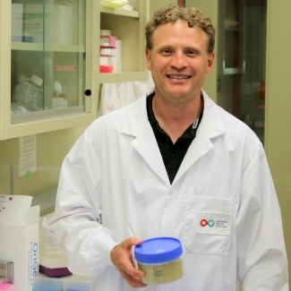 Dr Nicolas Pineault wears a lab coat and holds a blue plastic container in a stem cell lab