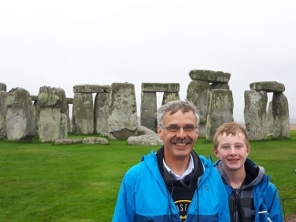 Dr. Blake and his son posing with the UK Stonehenge behind them