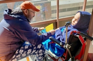 Mario and his son, Ollie, get some fresh air on the balcony of their condo in Toronto. The family is hoping Ollie can soon receive a transplant of stem cells from Ollie's sister Abby.