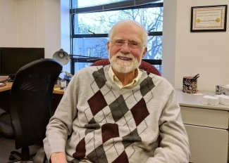 Dr. Michael McDonald sits in his office. He is wearing an Argyle sweater vest and has a white beard.