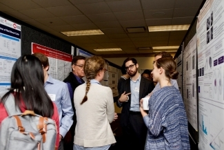 ttendees discuss posters during the 13th annual Earl W. Davie Symposium.