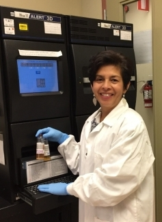 Dr. Ramirez  in the lab with the BacT/ALERT bacterial screening system.