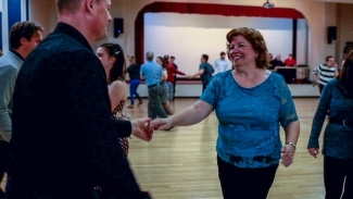 Image of Linda Paul holding her partners hand while swing dancing on the hardwood floor