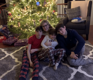 Image of Ty with his mom and two brothers at Christmas.