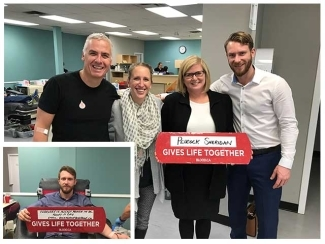 Peacock Sheridan Group at a donor centre posing together and hoping up a Gives Life Together sign.