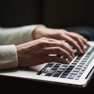 A woman's hands type on a laptop keyboard