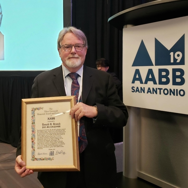 Dr. Donald Branch holds his award at the AABB annual meeting in San Antonio
