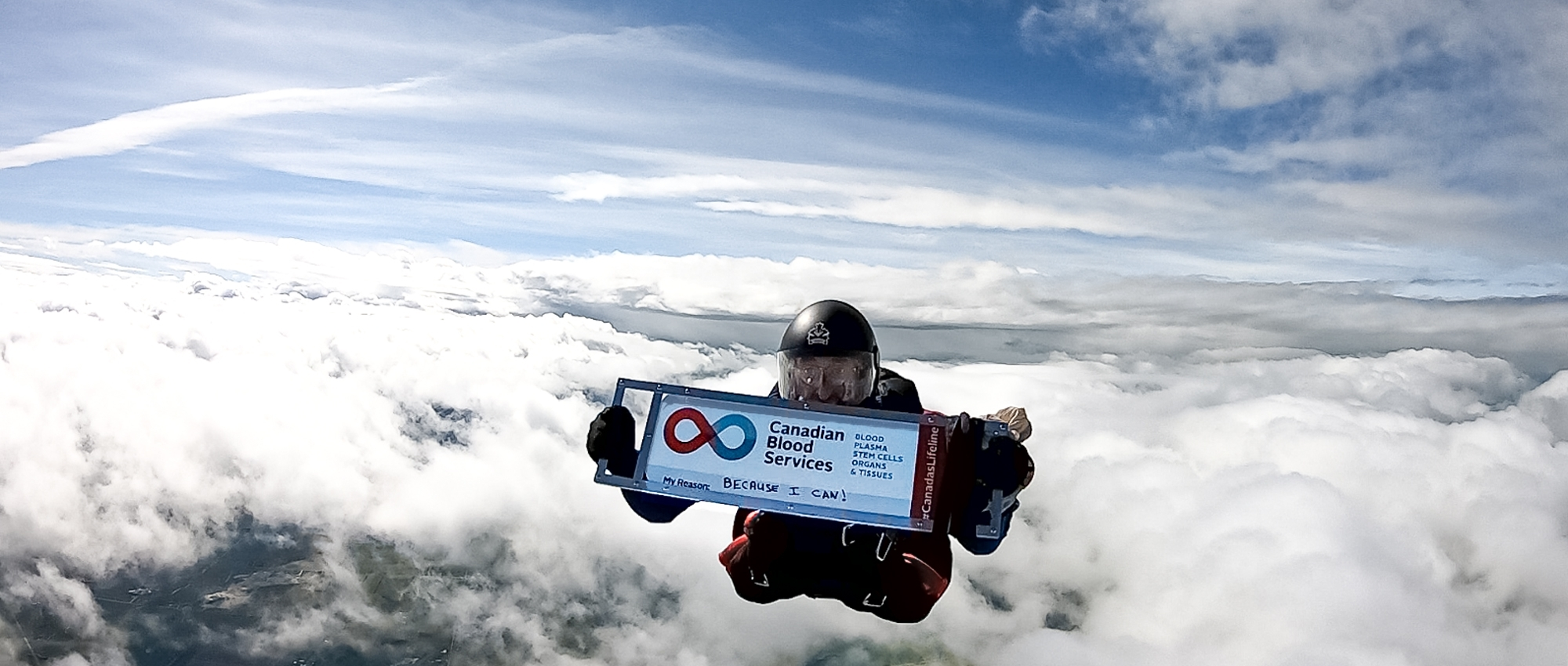 Big Image of Ian Harrop holding up a sign of Canadian Blood Services of his 600th blood donation while skydiving