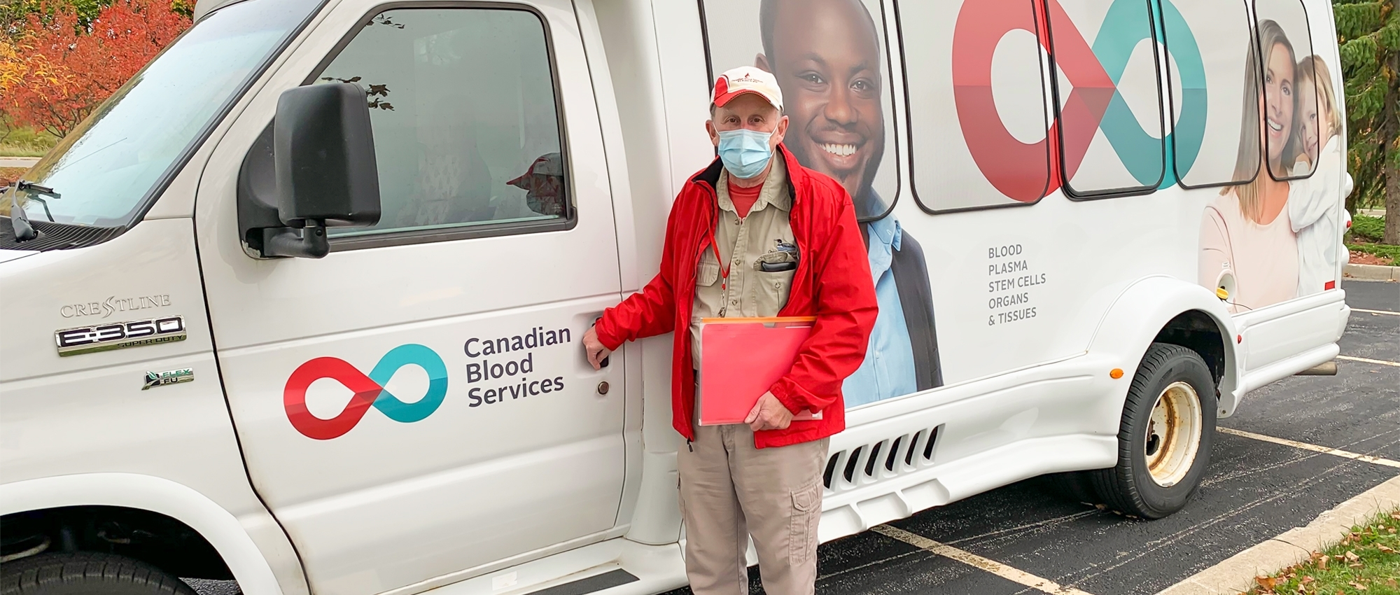 Image of Volunteer bus driver David Neu wearing a mask and holding a clipboard stands at the driver-side door of a short white bus with the Canadian Blood Services logo.