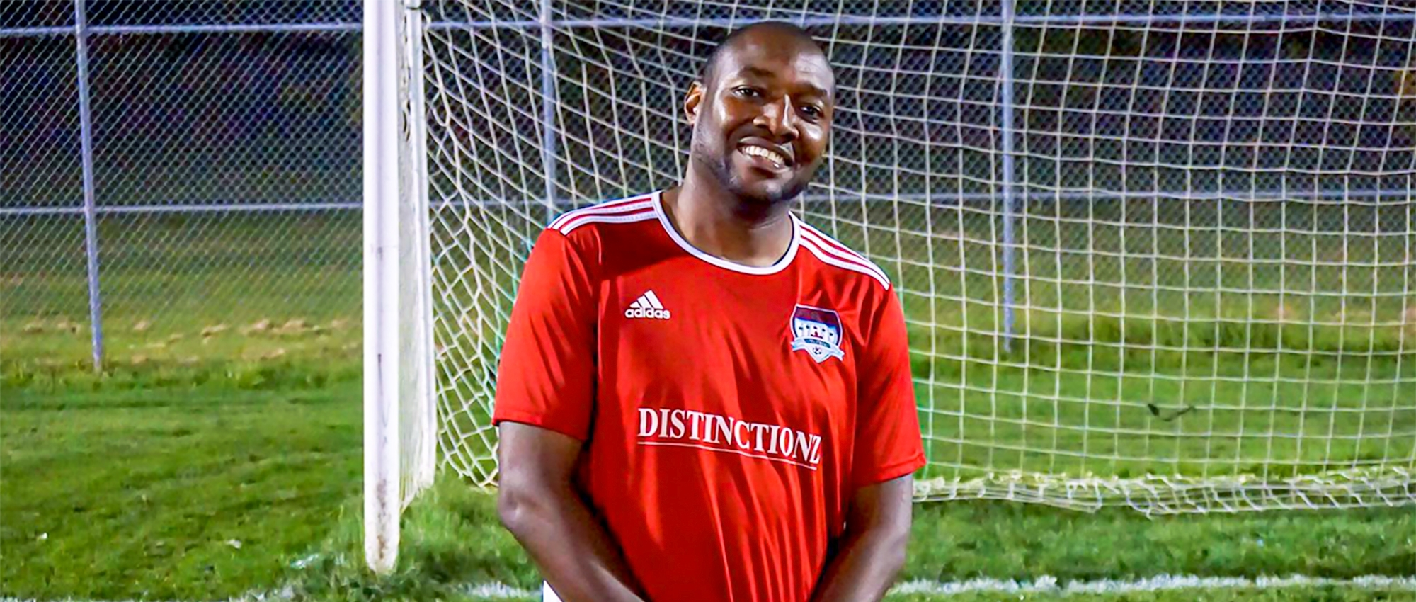 Featured image of Dujon Donaldson wearing a red soccer uniform in front of a soccer goal post