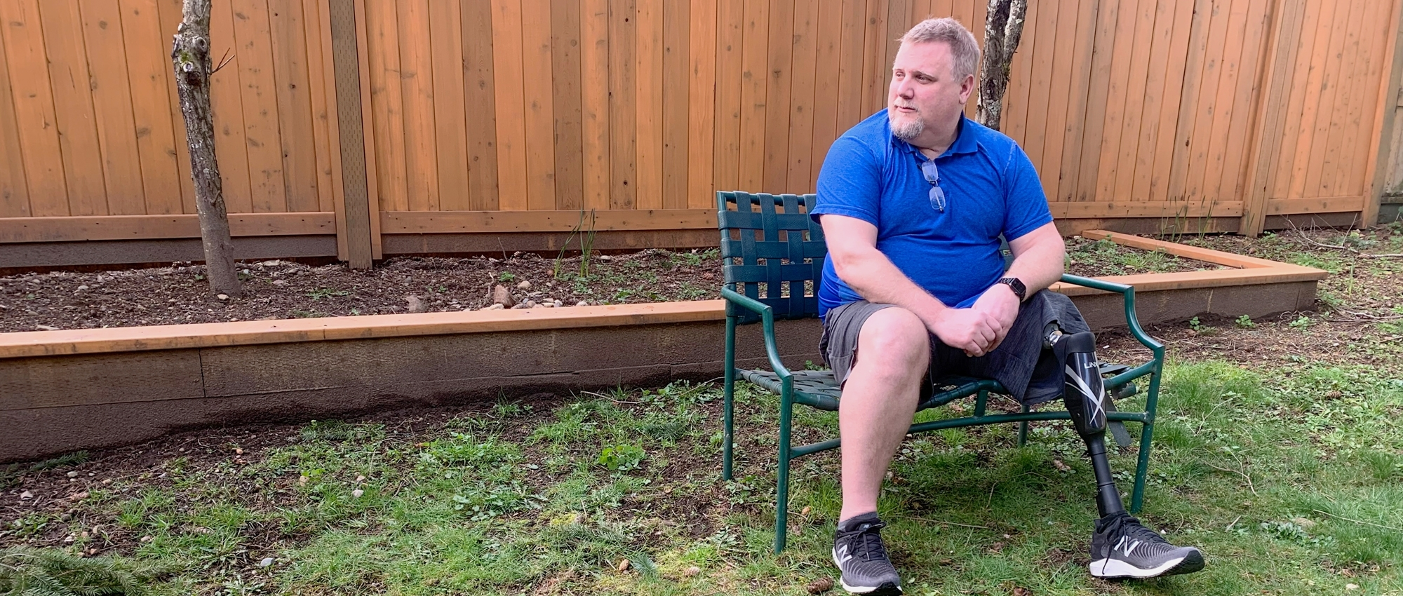 A man with a prosthetic leg sits on a bench outdoors.