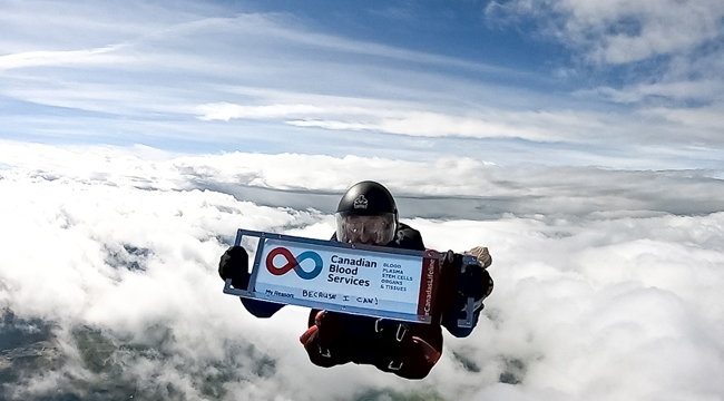 Image of Ian Harrop holding up a sign of Canadian Blood Services of his 600th blood donation while skydiving