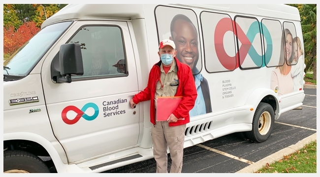 Image of Volunteer Life Bus driver David Neu standing outside of a Canadian Blood Services branded bus