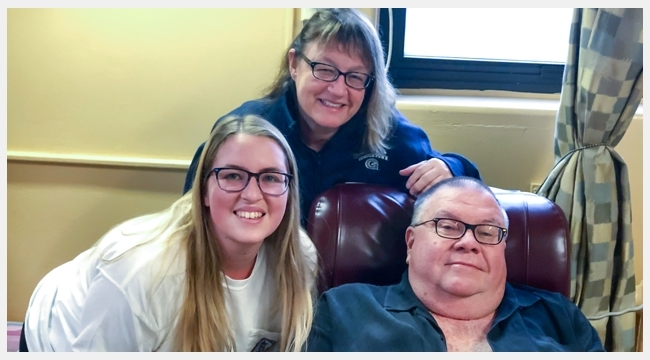 Image of Bruce Phinney with wife and daughter sitting in a recliner