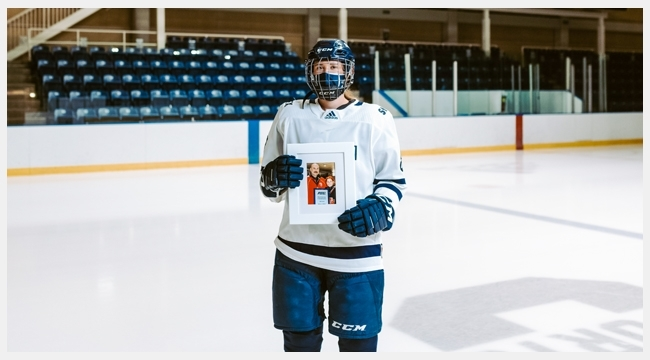 Image of Julia Schmitt holding up a picture frame of her and her dad wearing hockey equipment in an indoor hockey rink.