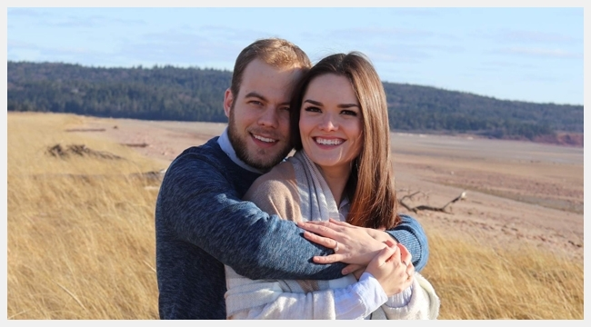 Lizzy Burns and her fiancé Ryan Doucet stand together in a field of yellow grasses. Lizzy Burns successfully donated stem cells in December 2020.