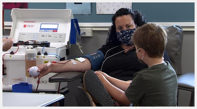 Shannon Morrison donates plasma while her son Heydan looks at her. Heydan receives medication made from plasma.