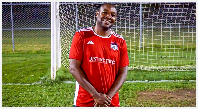 Image of Dujon Donaldson wearing a red soccer uniform in front of a soccer goal post