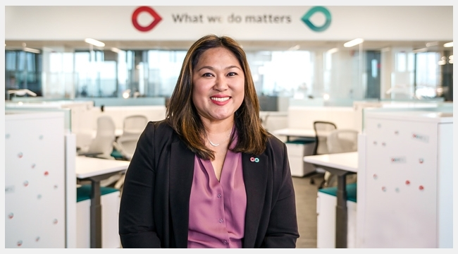 Thumbnail image of close up Territory manager for Calgary, Alberta, Jhoanna Del Rosario sitting in the Workplace of the Future at the new Canadian Blood Service Operational Facility