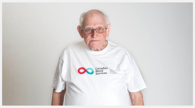 Thumbnail image of Bob Kerr wearing a Canadian Blood Services T-shirt standing in front of a white wall.