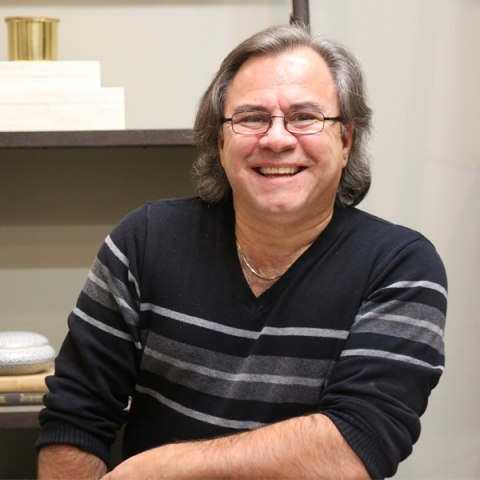 Image of blood donor Palmo Carpino sitting in front of a shelf wearing glasses and a striped sweater