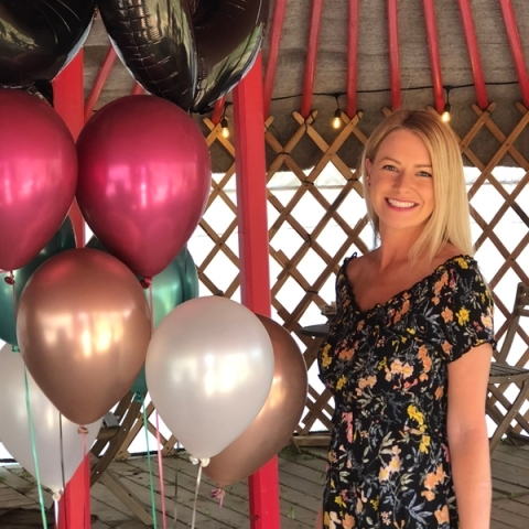 Image of blood donor Quinn Bleakley standing beside pink, teal, black, white, and gold balloons