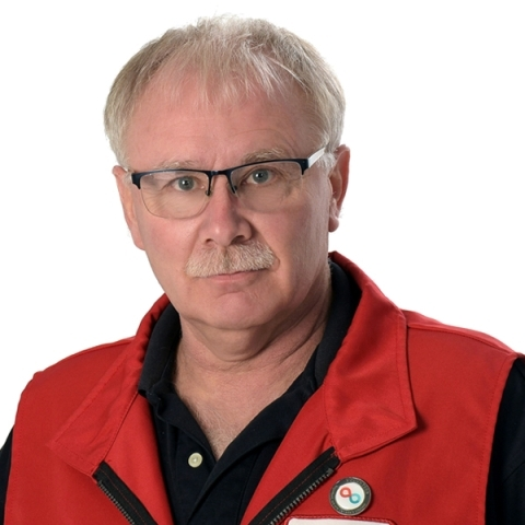 Photo of blood donor and volunteer Stephen Gregg with rectangular glasses and wearing a red Canadian Blood Services vest.