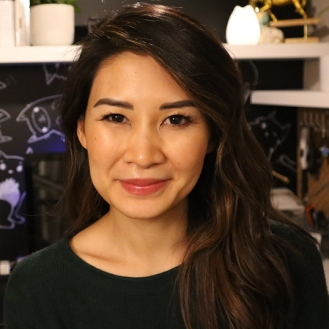 Photo of Susan Nguyen standing in front a desk in a bedroom with shelves
